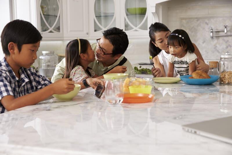 Fader Leaving For Work efter familjfrukost i kök royaltyfri bild