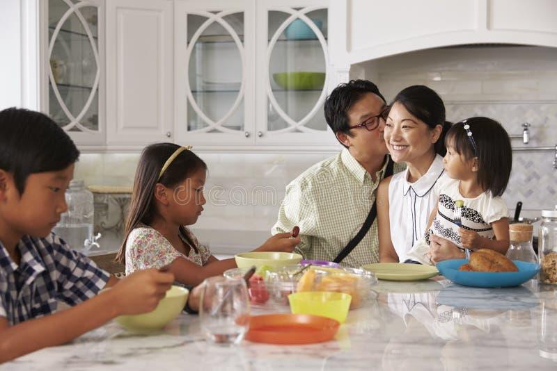 Fader Leaving For Work efter familjfrukost i kök royaltyfri fotografi