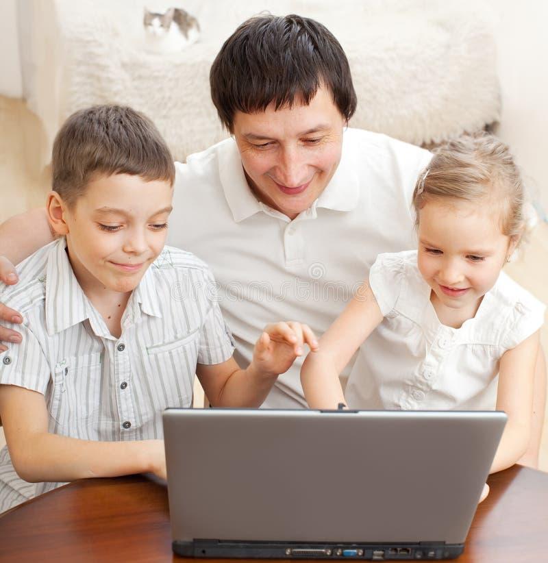 Fader med barn med bärbara datorn royaltyfri bild