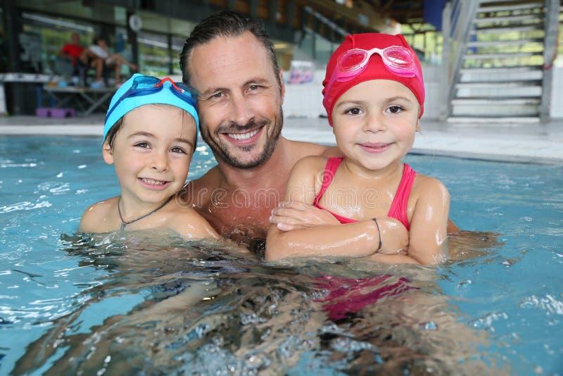 Fader med barn som är lyckliga i simbassäng arkivbilder