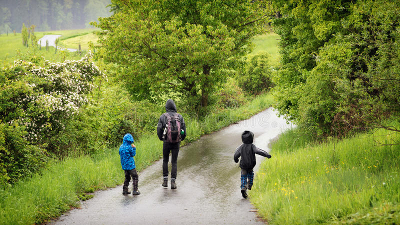 Fader med barn som går i regn fotografering för bildbyråer