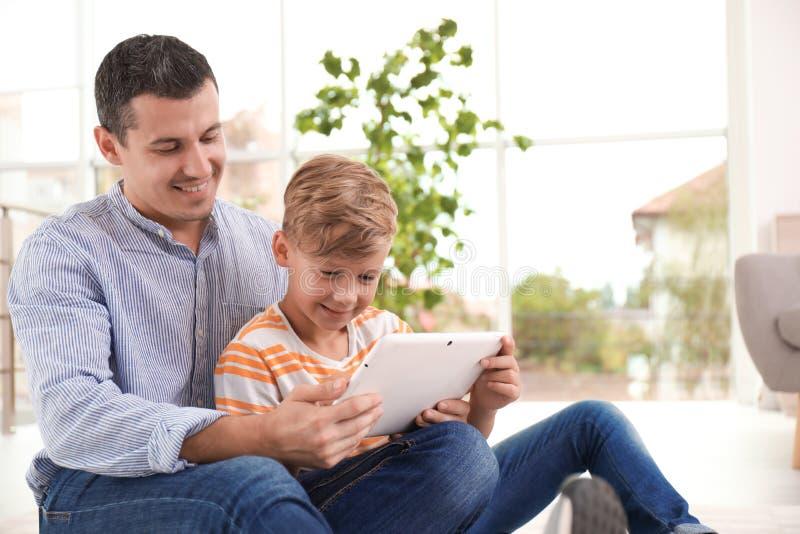 Fader med barnet som hemma använder minnestavlan royaltyfri fotografi