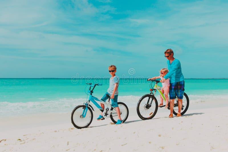 Fader med den lilla sonen och dottern som cyklar p? stranden arkivbilder