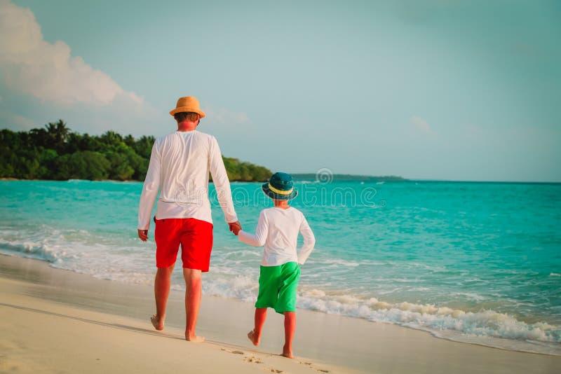 Fader med den lilla sonen som går på stranden fotografering för bildbyråer