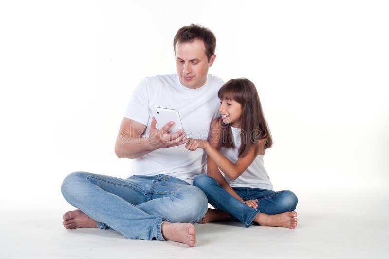 Fader med dottern som använder den digitala minnestavlan arkivfoto