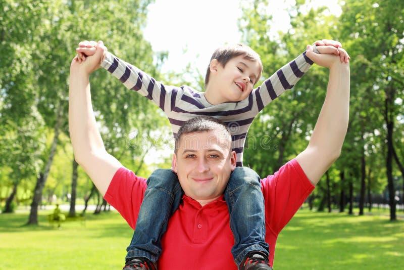 Fader med hans son i parkera fotografering för bildbyråer