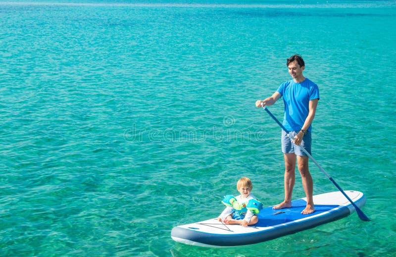 Fader med hans son på SUP Plattfor paddla upp royaltyfri foto