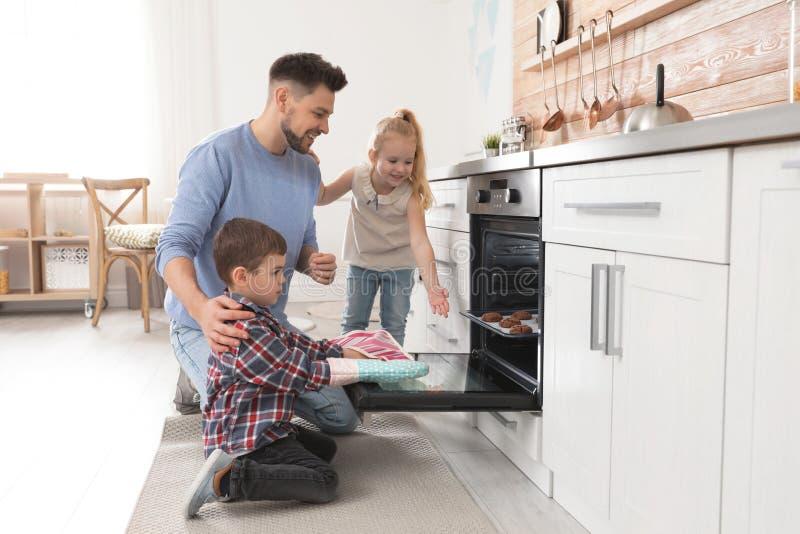 Fader med hans ungar som bakar kakor i ugn royaltyfri foto