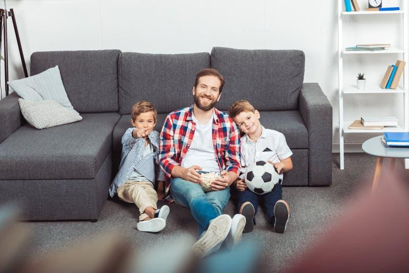 fader med söner som äter popcorn, medan hålla ögonen på fotbollsmatchen fotografering för bildbyråer