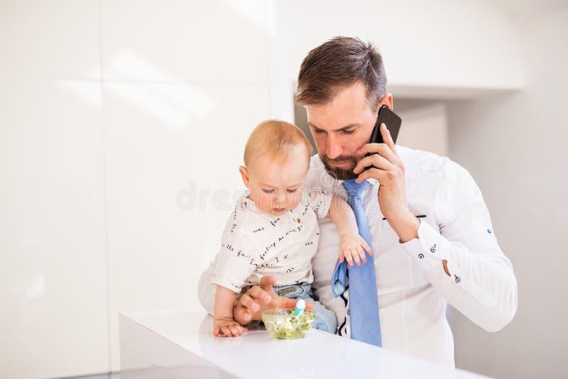 Fader med skjortan och bandet och smartphone som hemma matar en behandla som ett barnson, när tala på telefonen arkivfoton