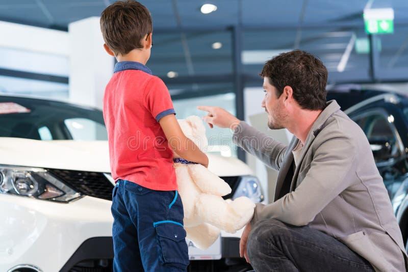 Fader med sonen i visningslokal för bilåterförsäljare royaltyfria foton