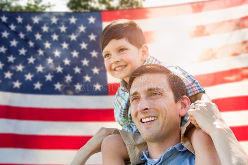 Fader med sonen som på ryggen framme rider av amerikanska flaggan royaltyfria bilder