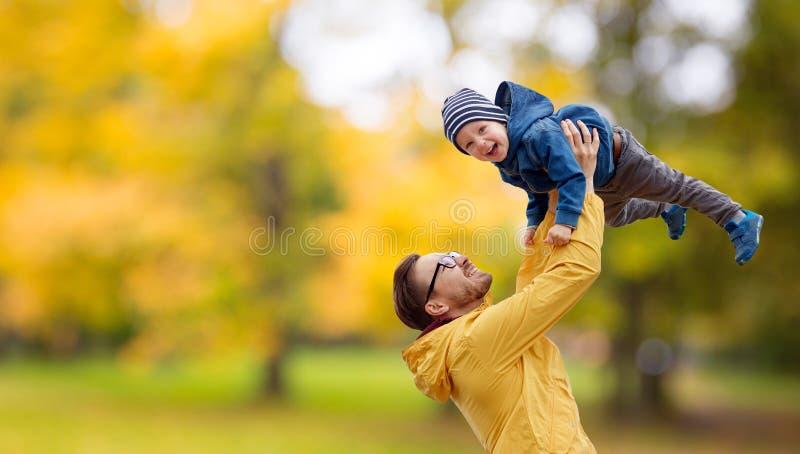 Fader med sonen som spelar och har gyckel i höst fotografering för bildbyråer