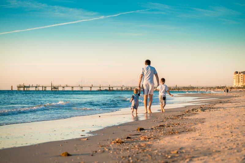 Fader med två söner som går på stranden royaltyfria bilder
