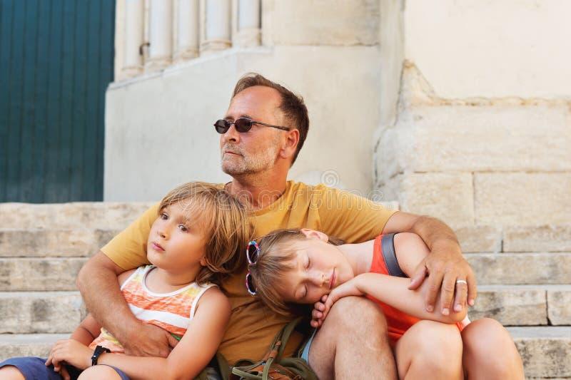 Fader med två tröttade ungar som utanför vilar royaltyfria bilder