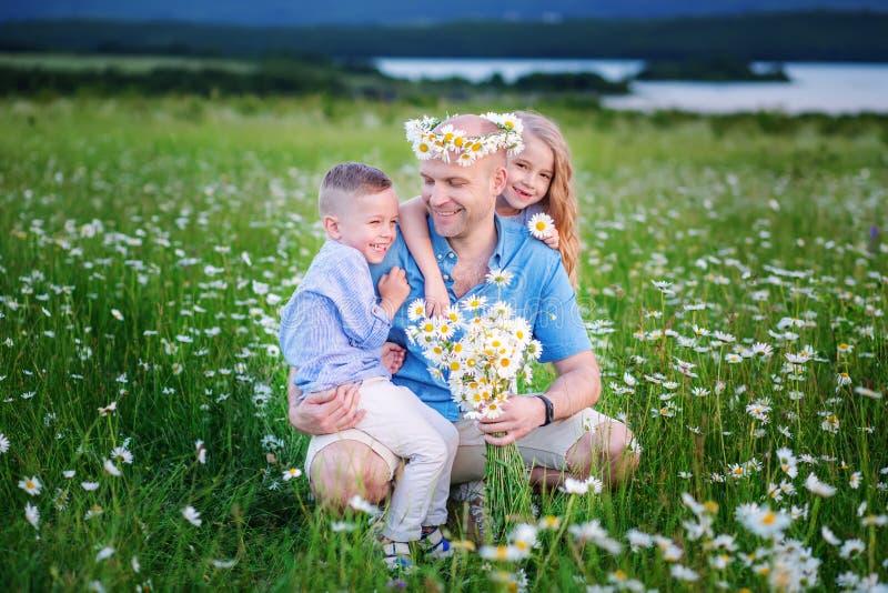 Fader och barn på den offroad bilen som spelar i fältet efter su royaltyfri fotografi