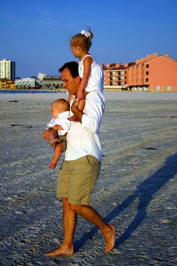 Fader och barn på stranden arkivbild