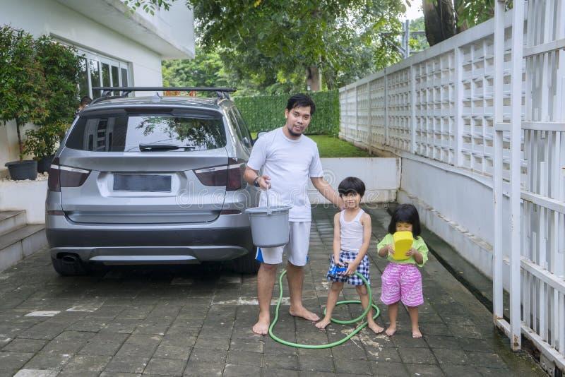 Fader och barn som är klara att tvätta en bil arkivfoto