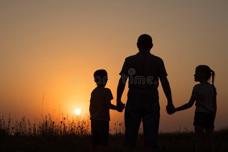 Fader och barn som spelar i parkera på solnedgångtiden arkivbild