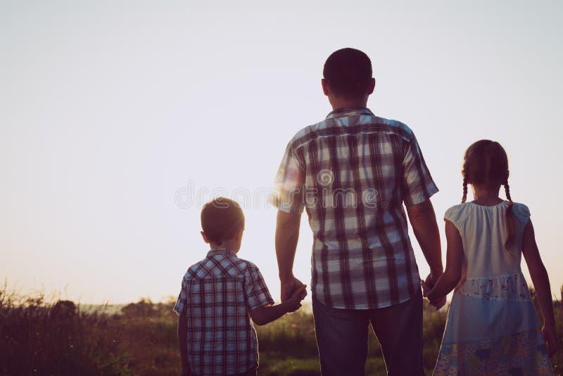 Fader och barn som spelar i parkera på solnedgångtiden fotografering för bildbyråer