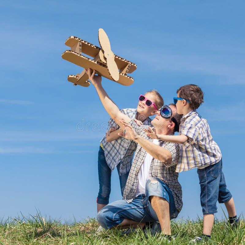 Fader och barn som spelar med pappleksakflygplanet i pet royaltyfria bilder