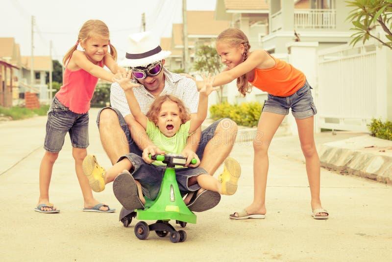Fader och barn som spelar nära ett hus royaltyfri bild