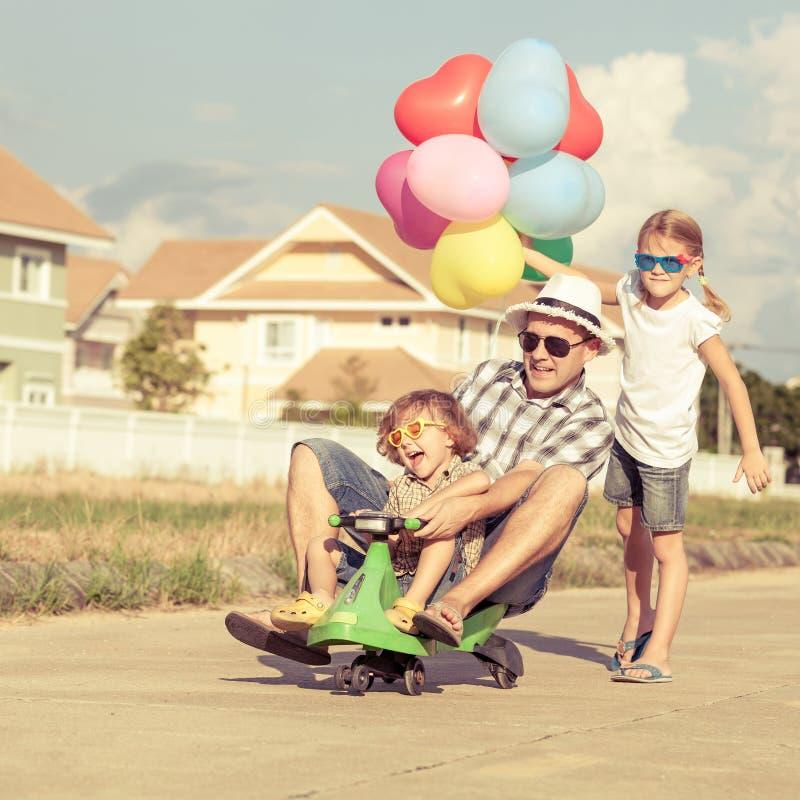 Fader och barn som spelar nära ett hus fotografering för bildbyråer