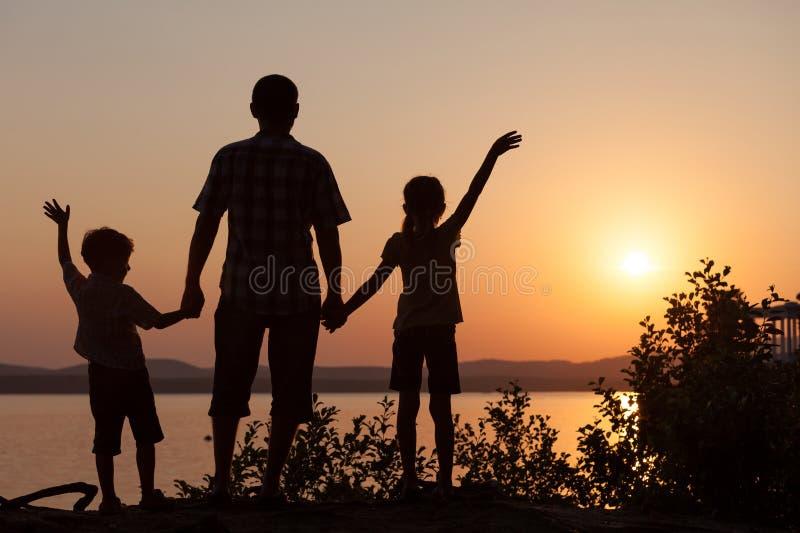 Fader och barn som spelar på kusten av sjön royaltyfria foton
