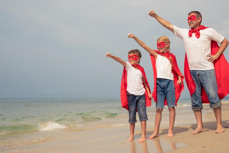 Fader och barn som spelar superheroen på stranden på dagsi fotografering för bildbyråer