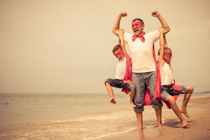 Fader och barn som spelar superheroen på stranden på dagsi arkivbild