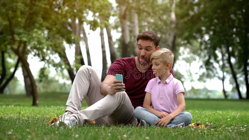 Fader och barn som tar selfie med smartphonen som fångar lyckligt familjögonblick arkivbilder