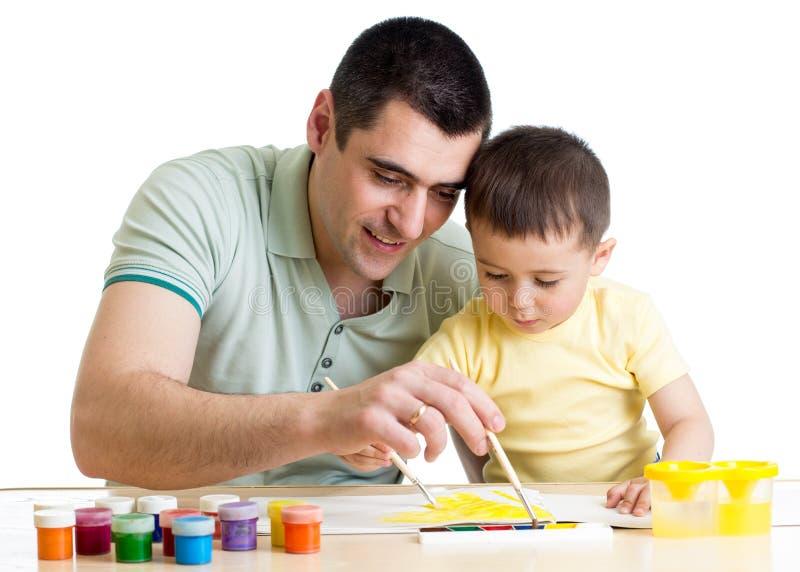 Fader- och barnpojken målar tillsammans arkivfoto