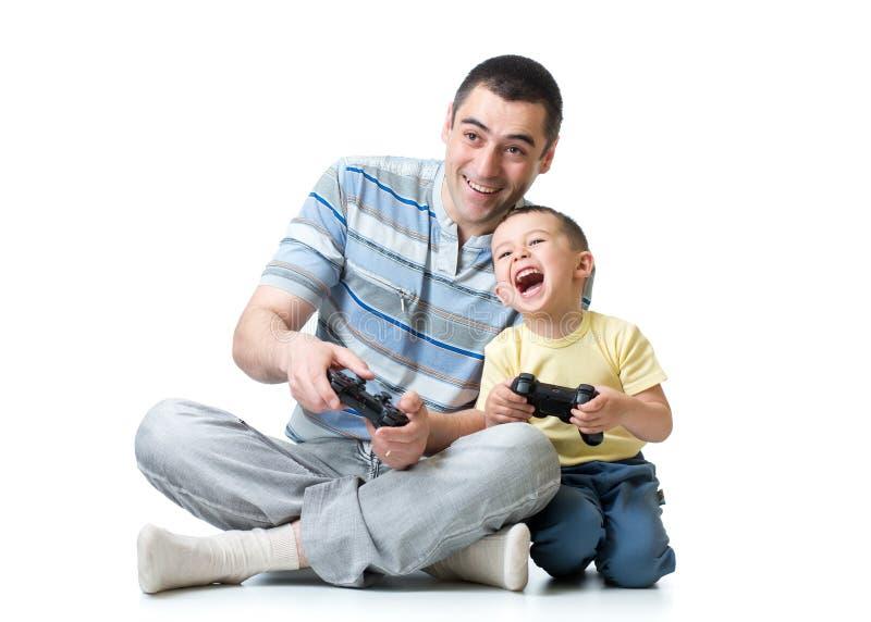 Fader- och barnson som hemma spelar videogamen arkivbilder