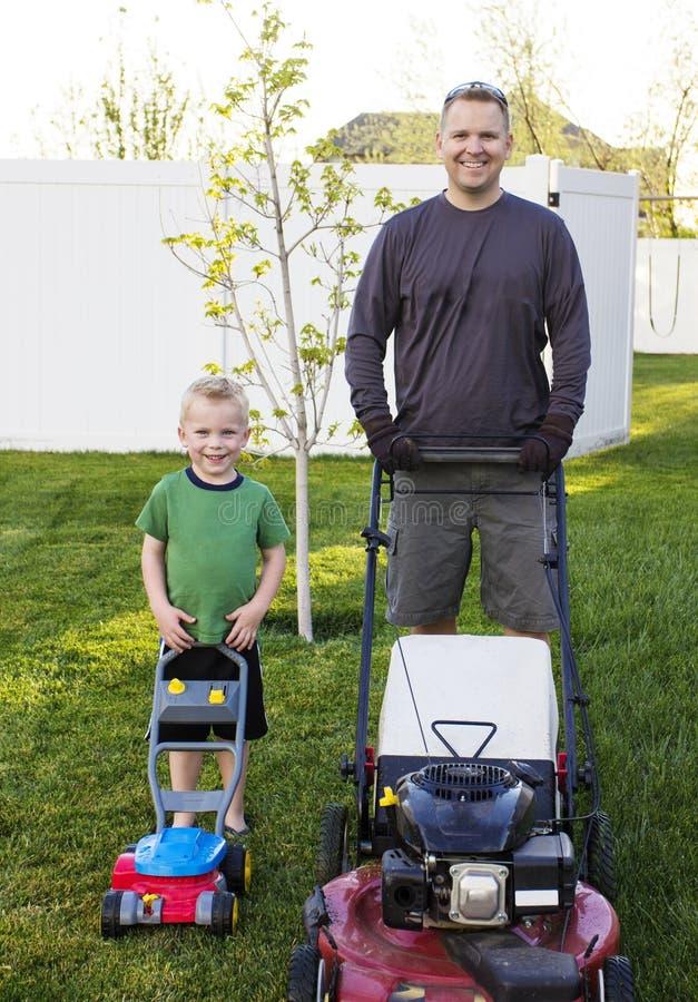 Fader och barnson som tillsammans mejar gräsmattan arkivbild