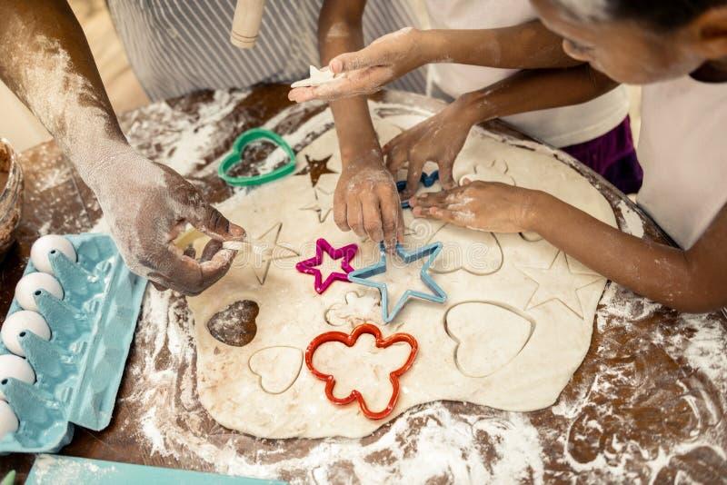Fader och döttrar som har händer i mjöl, medan göra kakor arkivfoton