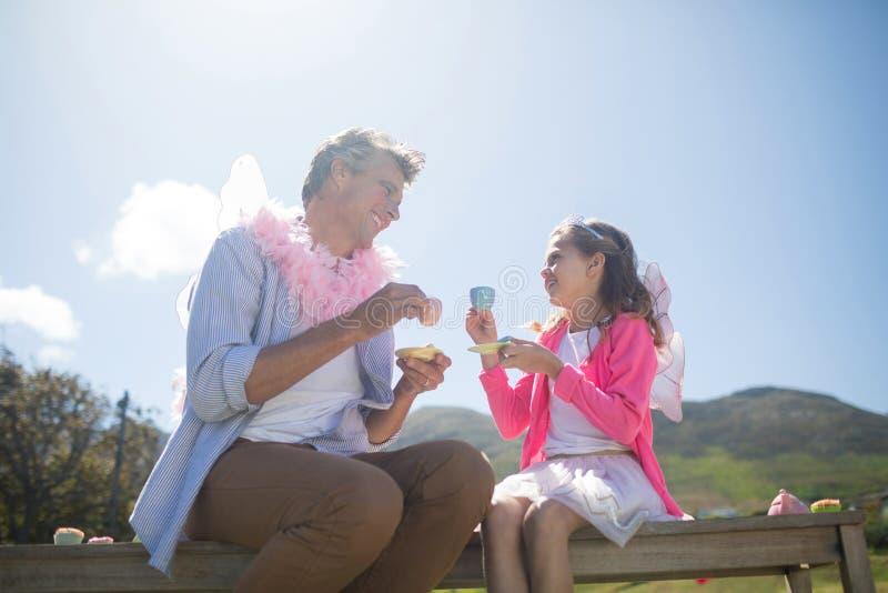 Fader och dotter i den felika dräkten som har en tebjudning royaltyfria foton