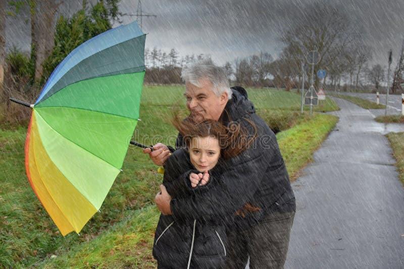 Fader och dotter i stormigt väder arkivfoto
