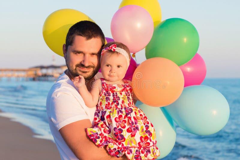 Fader och dotter med ballonger som spelar på stranden på dagtiden Begrepp av den vänliga familjen royaltyfri bild