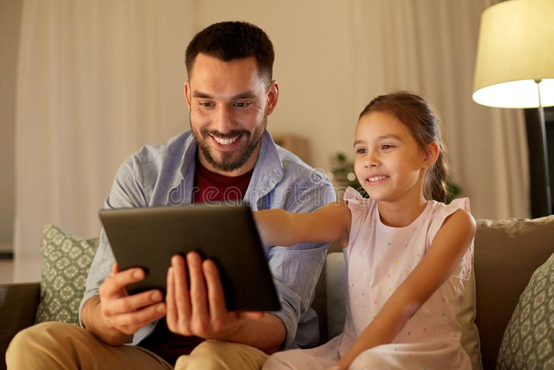 Fader och dotter med minnestavladatoren hemma arkivfoto