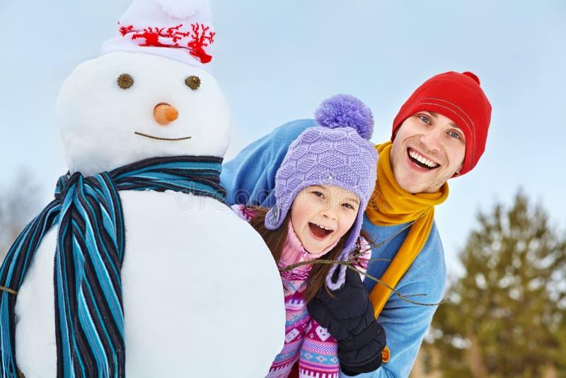 Fader och dotter med snögubben arkivfoton
