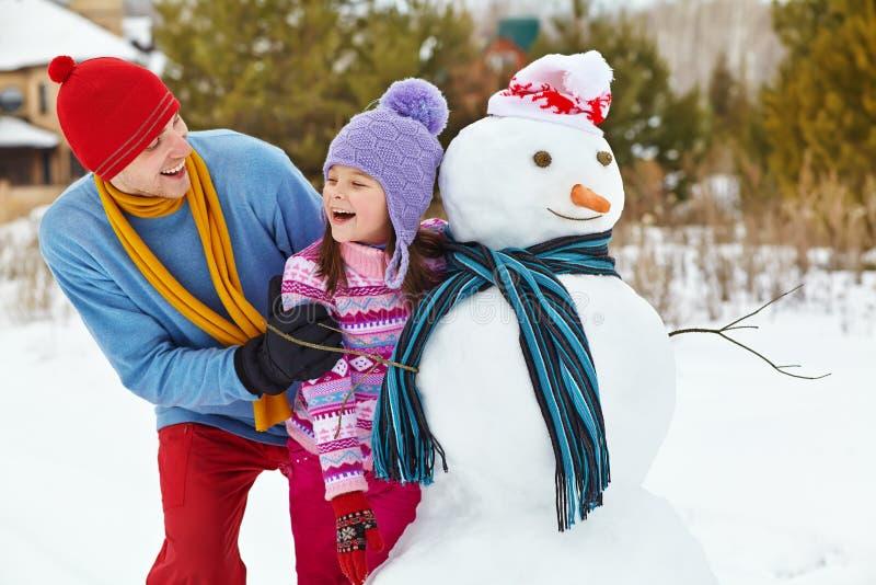 Fader och dotter med snögubben royaltyfri bild