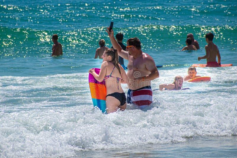 Fader och dotter med surfingbrädan, medan barnet tycker om vågorna fotografering för bildbyråer