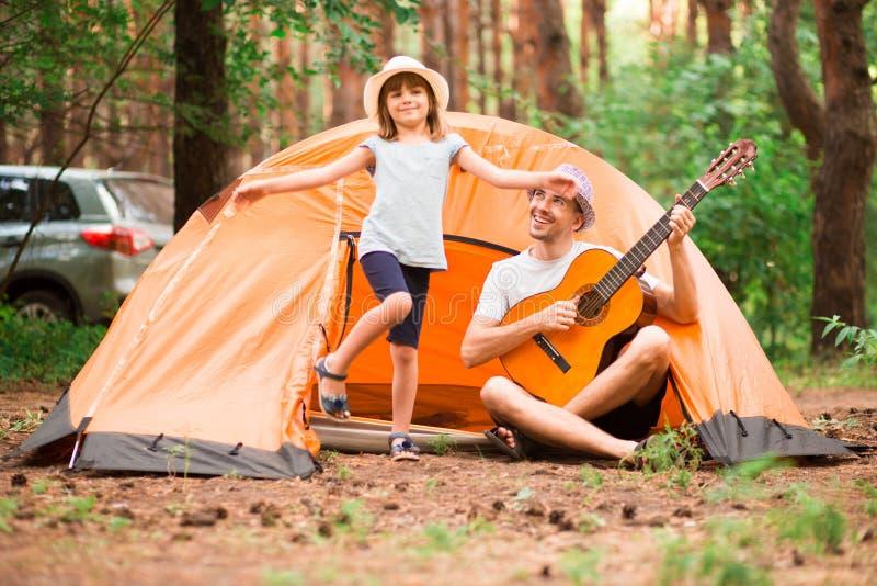 Fader och dotter nära det campa tältet som spelar gitarren fotografering för bildbyråer