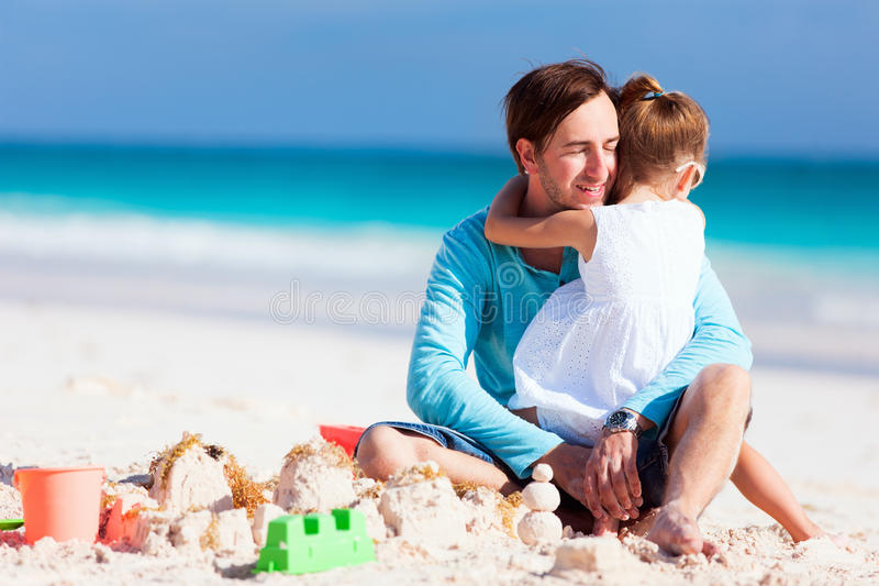 Fader och dotter på en strand royaltyfria bilder