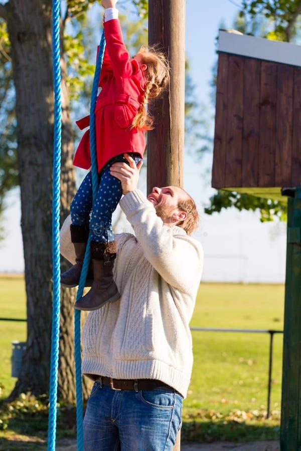 Fader och dotter på lekplats arkivbilder