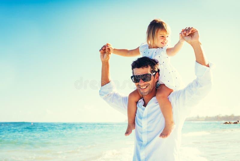 Fader och dotter på stranden royaltyfri bild