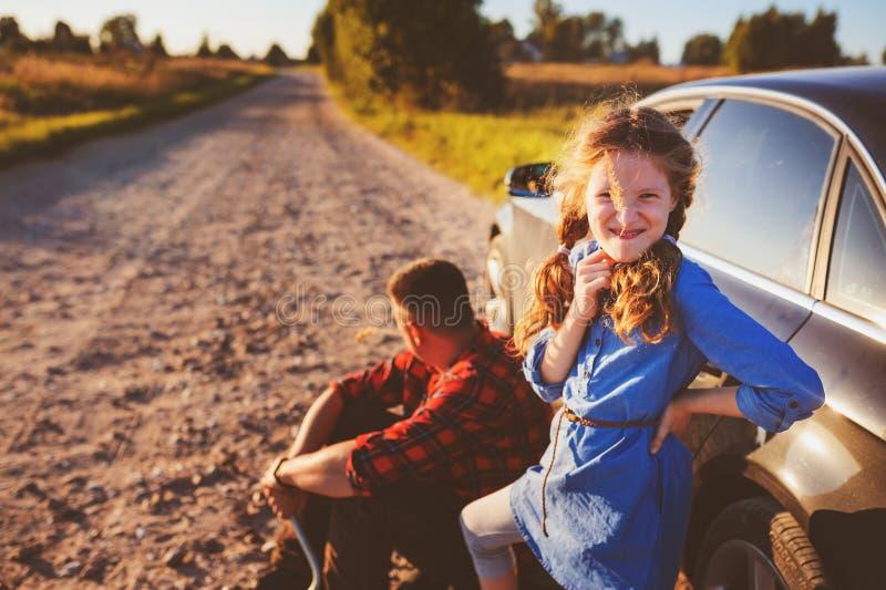 Fader och dotter som ändrar det brutna gummihjulet under lantlig vägtur för sommar royaltyfria foton
