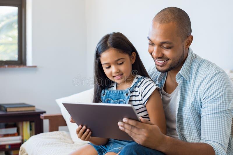 Fader och dotter som använder minnestavlan arkivfoto