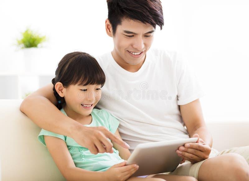 Fader och dotter som använder minnestavlan på soffan royaltyfri fotografi