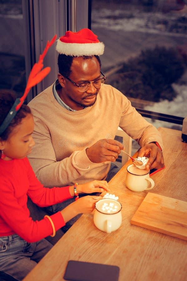 Fader och dotter som dricker smaklig kakao med marshmallower royaltyfri bild